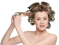Woman curling her hair with roller Royalty Free Stock Photos