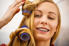 Woman curling her hair using rollers Stock Photos