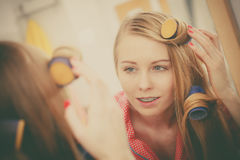 Woman curling her hair using rollers Royalty Free Stock Photography