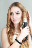Woman curls her hair Stock Photos