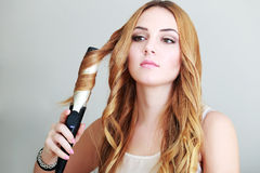 Woman curls her hair Royalty Free Stock Photos