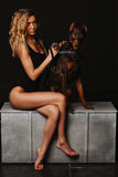 Woman with curly blond hair in a black bathing suit sitting with Doberman. A girl holding a Doberman the chain. Long Royalty Free Stock Photography