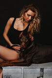 Woman with curly blond hair in a black bathing suit sitting with Doberman. A girl holding a Doberman the chain. Long Royalty Free Stock Images