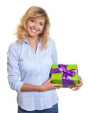Woman with curly blond hair and christmas gift Royalty Free Stock Photo
