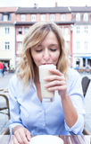 Woman with curly blond hair drinks coffee latte Royalty Free Stock Image