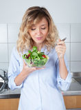 Woman with curly blond hair eating salad in the kitchen Royalty Free Stock Photo