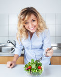 Woman with curly blond hair preparing salad in the kitchen Royalty Free Stock Photo