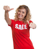 Woman with curly blond hair and sales-shirt showing both thumbs
