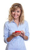 Woman with curly blond hair sending message with phone Stock Image
