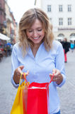 Woman with curly blond hair and shopping bags in the city Stock Images