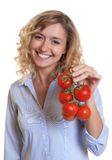 Woman with curly blond hair and tomatoes in her hand Stock Images