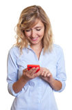 Woman with curly blond hair writing message with phone Stock Images