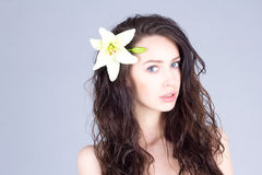 Woman with curly brown hair and a flower in her hair Stock Photo