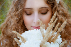Woman with curly golden hair smiling with a bee on her pupils Stock Photography