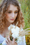 Woman with curly golden hair smiling standing in the field Stock Image