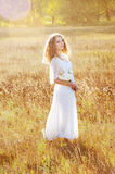 Woman with curly golden hair smiling standing in the field Royalty Free Stock Images