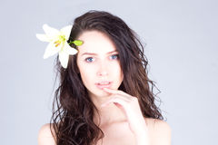 Woman with curly hair and big blue eyes touching lips. Woman with a flower in her hair. Royalty Free Stock Photography