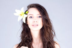 Woman with curly hair and big blue eyes. Woman with a flower in her hair. Stock Photos
