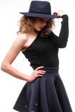 Woman with curly hair in black hat and stylish elegant evening dress Stock Photo
