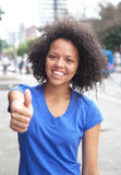 Woman with curly hair in the city showing thumb Stock Photo