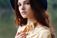 Woman with curly hair and floppy hat Stock Image