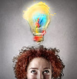 Woman with curly hair having an idea. Youngwoman with curly hair having an idea and looking at the light bulb stock photos
