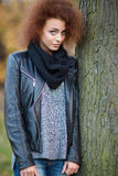 Woman with curly hair leaning on the tree outdoors Royalty Free Stock Photography