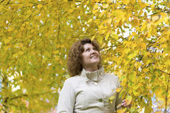 Woman with curly hair near autumn birch stock photo