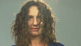 Woman with curly hair sits with eyes closed then suddenly opens them, awakening. Stock footage stock video footage