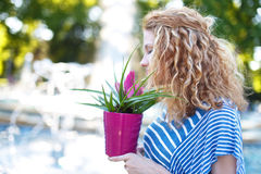 Woman with curly hair smell flower Stock Photos