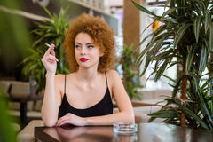 Woman with curly hair smoking in restaurant Royalty Free Stock Photo