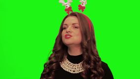 Woman with curly hair wearing nice dress, christmas stuff and necklace sings and smiles against chromakey. stock video footage
