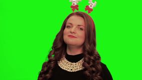 Woman with curly hair wearing nice dress, christmas stuff and necklace sings and smiles against chromakey. stock video