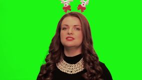 Woman with curly hair wearing nice dress, christmas stuff and necklace sings and smiles against chromakey. Woman with curly hair wearing nice black dress stock video footage