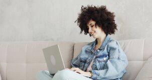Woman with curly hair writing message in social media on laptop sitting on sofa.