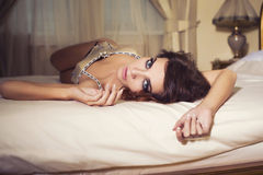 Woman with curly hairstyle laying on a floor near luxury bed Stock Photo