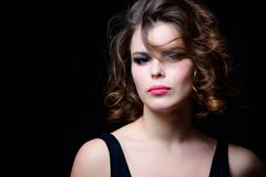 Woman with curly hairstyle and makeup on black background. Makeup idea for elegant outfit. Professional makeup. Attractive elegant lady with smoky eyes makeup stock photography