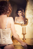 Woman with curly hairstyle standing near luxury mirror Royalty Free Stock Image