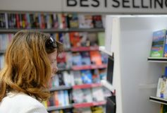 Member of there public seen looking at books as seen in a high-street newsagent and bookshop. The woman is currently looking at tour books. The background shows stock image