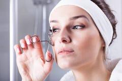 Woman curving eyelashes Stock Photo