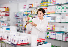 Woman customer browsing rows of drugs Royalty Free Stock Photo