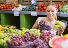 Woman customer buying sweet ripe grapes on marketplace Stock Photos