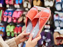 Woman customer chooses home slippers in shop Stock Photos