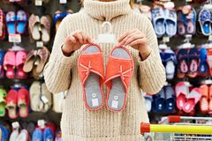 Woman customer chooses home slippers in shop Stock Photography