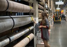 Woman customer choosing linoleum flooring in hypermarket. Smart woman customer choosing linoleum flooring in construction and repair hypermarket Stock Photos