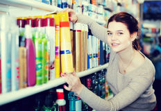 Woman customer deciding on hair care products in shop. Woman customer deciding on hair care products in cosmetics shop stock photo