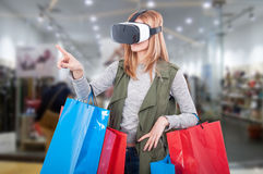 Woman customer experience virtual shopping. Thru modern headset and pointing finger at something Stock Photo