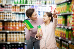 Woman customer with girl looking for refreshing beverages. Attractive young women customer with girl looking for refreshing beverages in supermarket royalty free stock photography