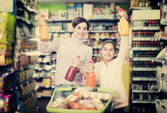 Woman customer with girl looking for refreshing beverages Stock Images
