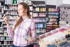 Woman customer holding glass jar with color paint in art departm Stock Photography